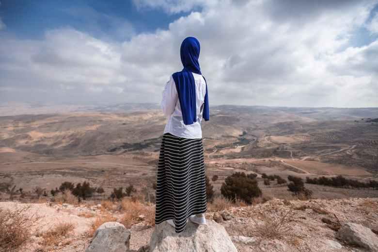 woman standing near beige cliff
