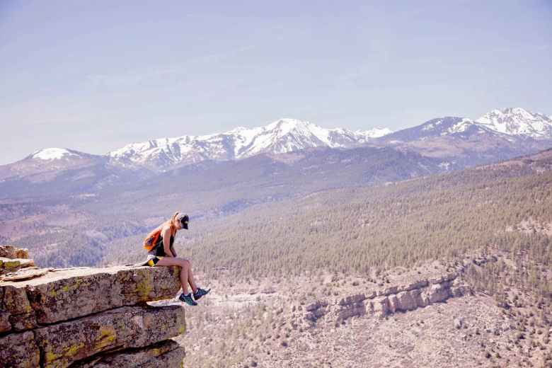 photography of a woman sitting on cliff