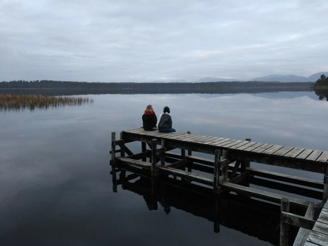 Two women travellers on the jetty of a lake