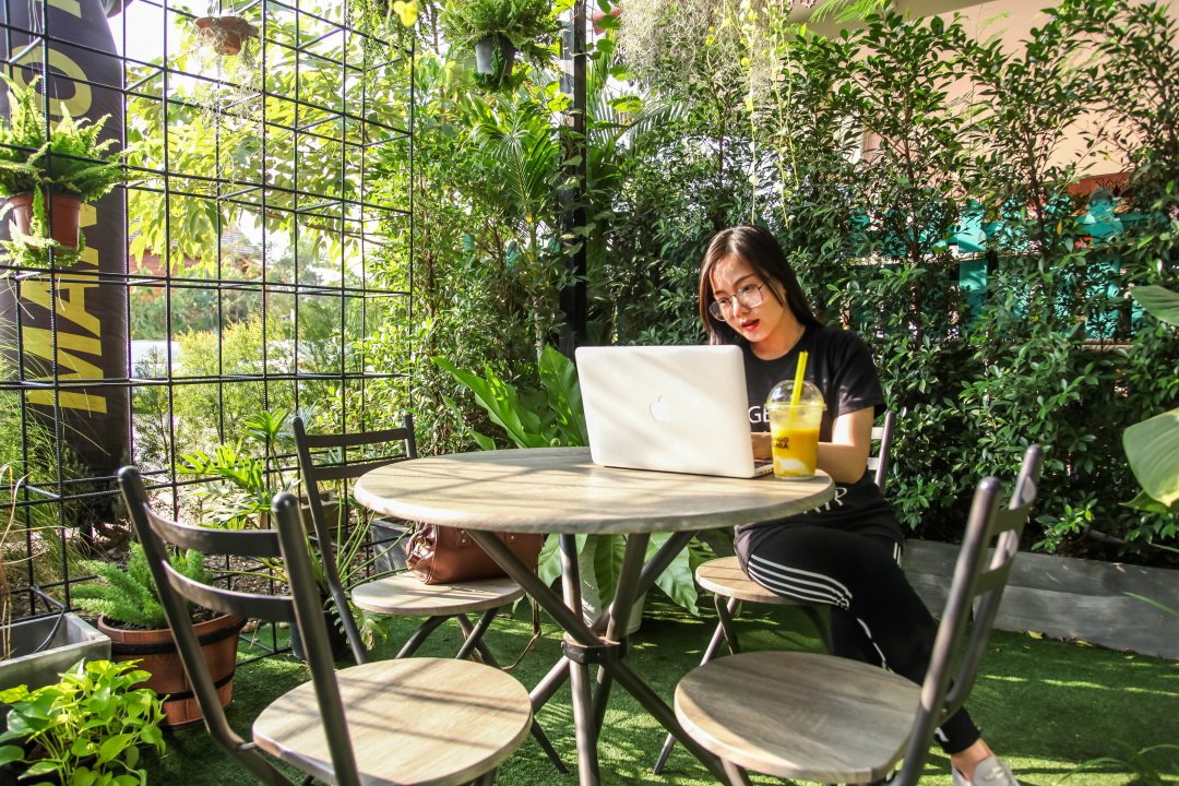 Woman blogging on her laptop on a table outside surrounded by plants.