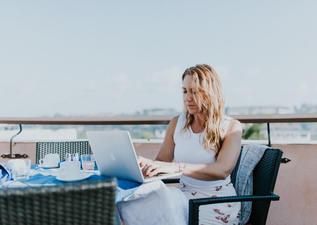How To Succeed In Travel Blogging And Other News - woman on her laptop at a table outside.